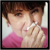 Foto de una mujer con alergias sosteniendo un pañuelo en la nariz