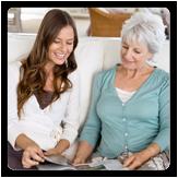 Mujer joven leyéndole a una mujer mayor